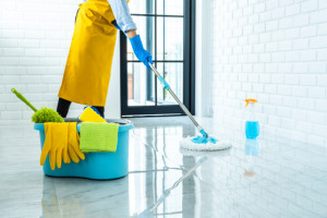 happy-young-woman-in-blue-rubber-using-mop-while-cleaning-on-floor-at-home_28283-1482